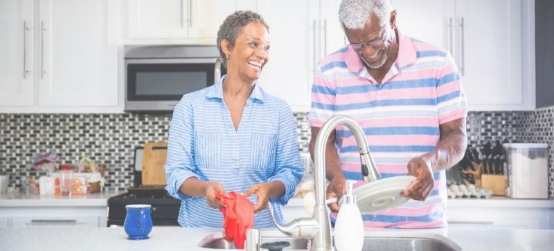 Image of an older couple washing dishing together and laughing